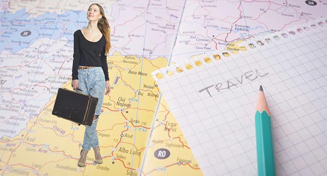 地図の上に旅行バッグを持った女性